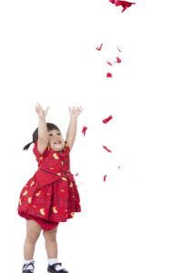 Flower falling on little girls head. kid girl enjoy with rain of flower isolated on white background.